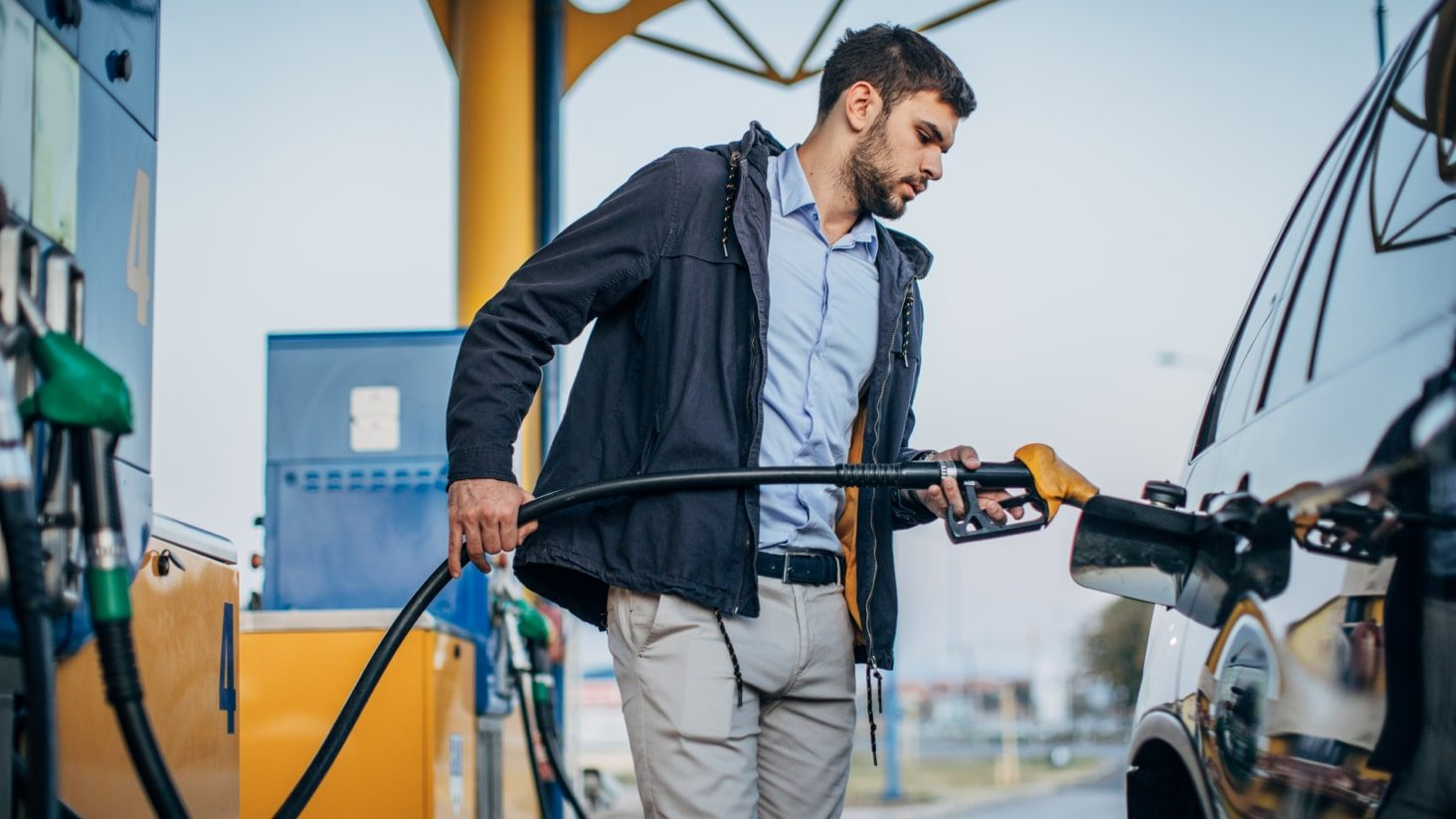 People filling up petrol on a road trip, considering budget plans.