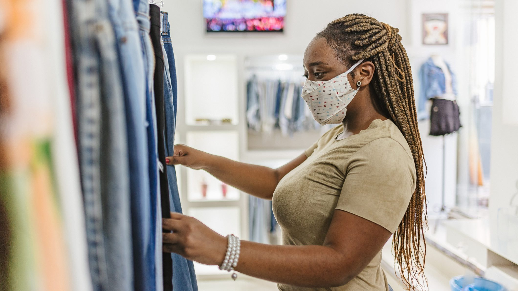 Person shopping for clothes in face mask as spending increases.