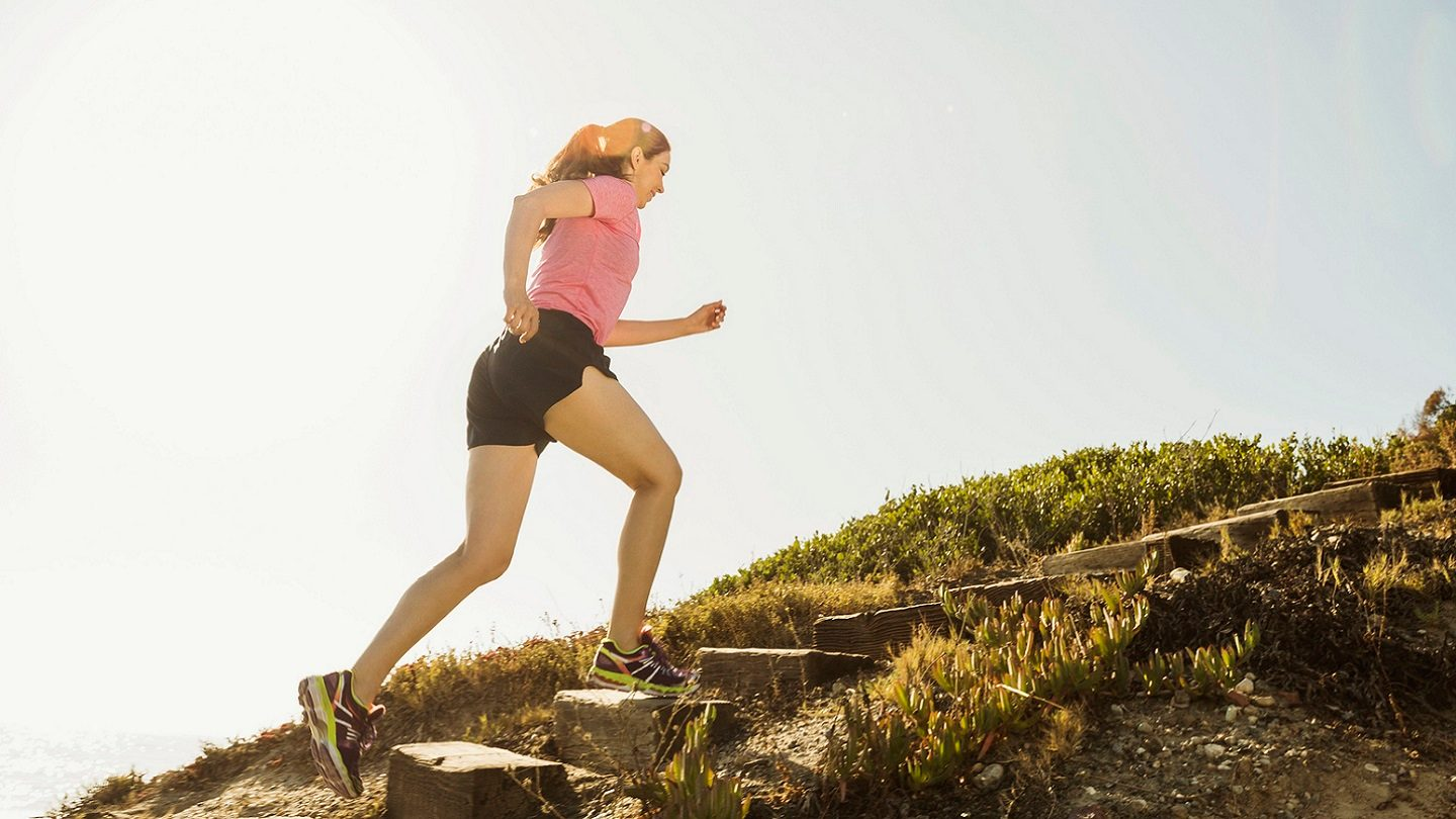 Woman jogging up stairs towards her new year's resolutions