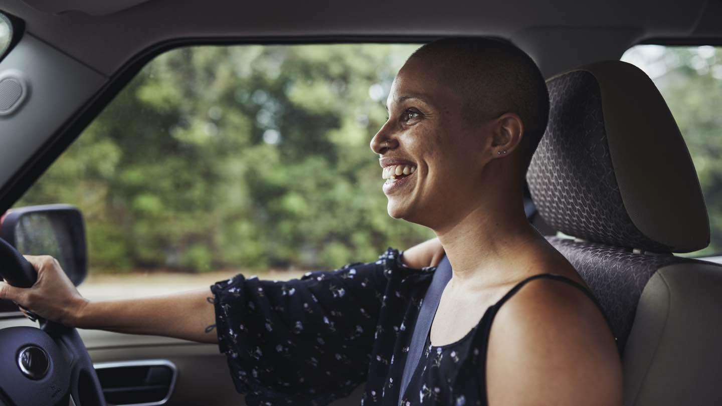 A woman smiles as she grips the steering wheel of her car.