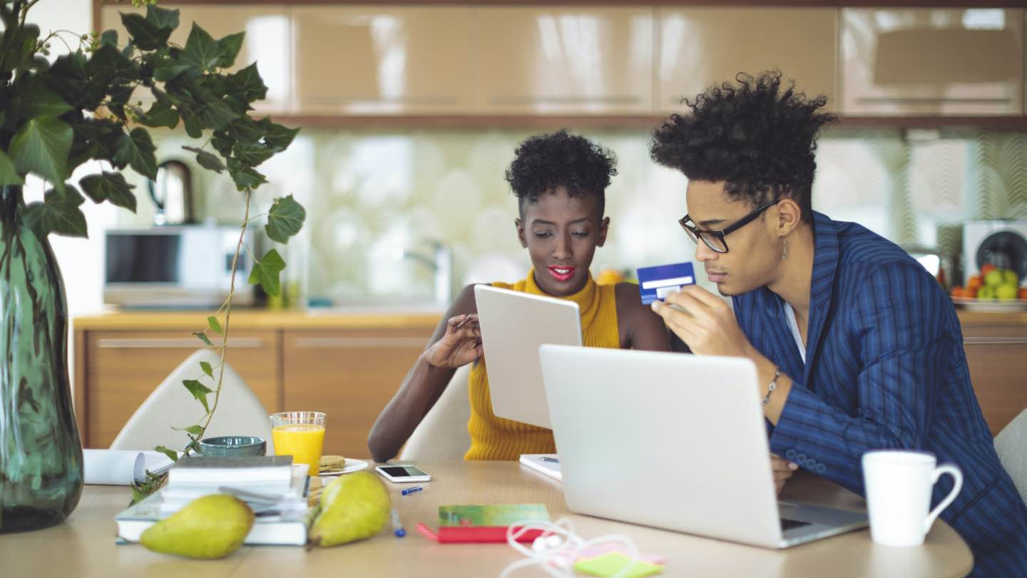 Man and woman sit at kitchen table with laptop and tablet, reviewing expenses for 2021.