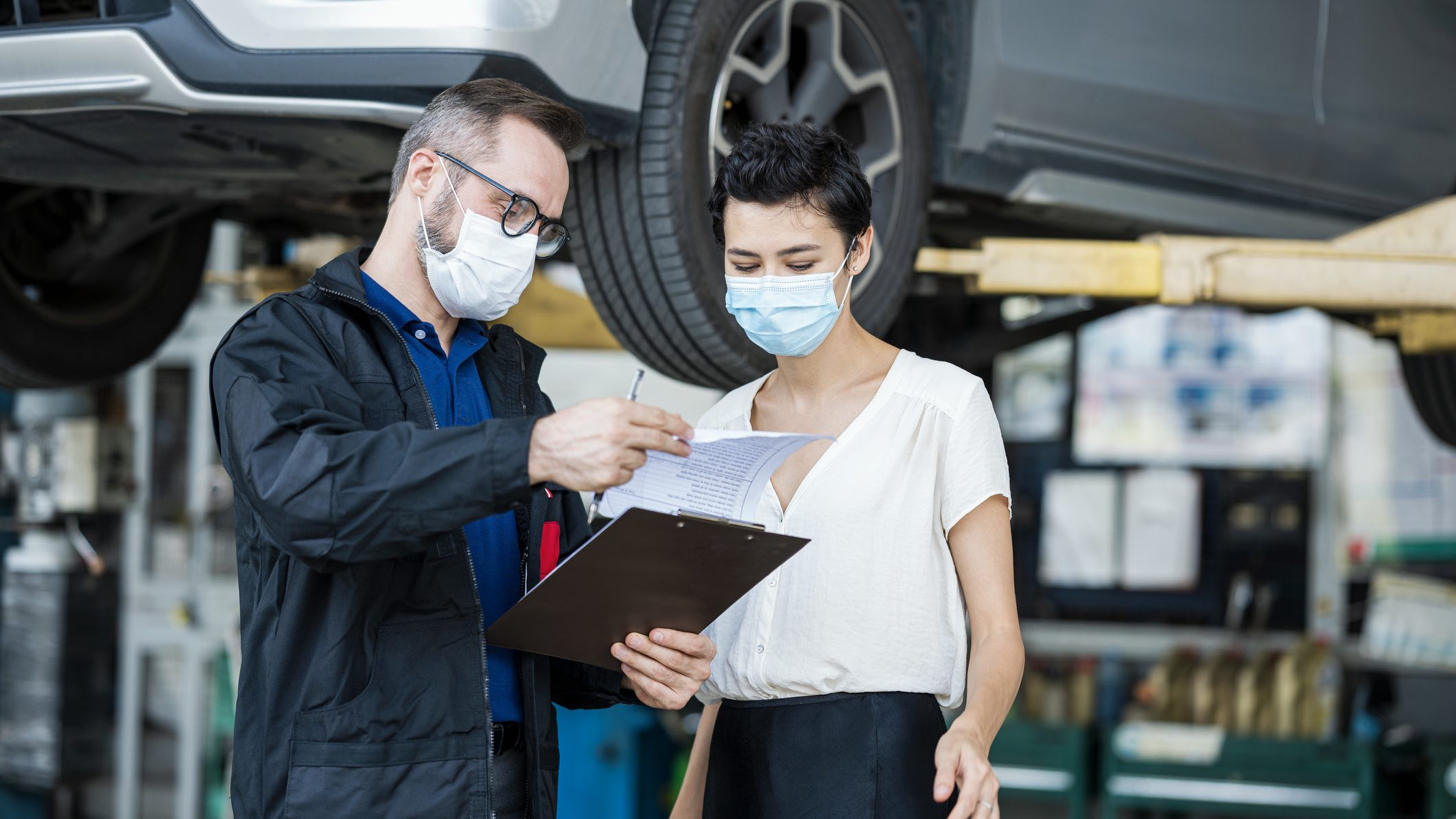 People in medical face masks looking at rising car insurance costs in front of a vehicle getting repairs.