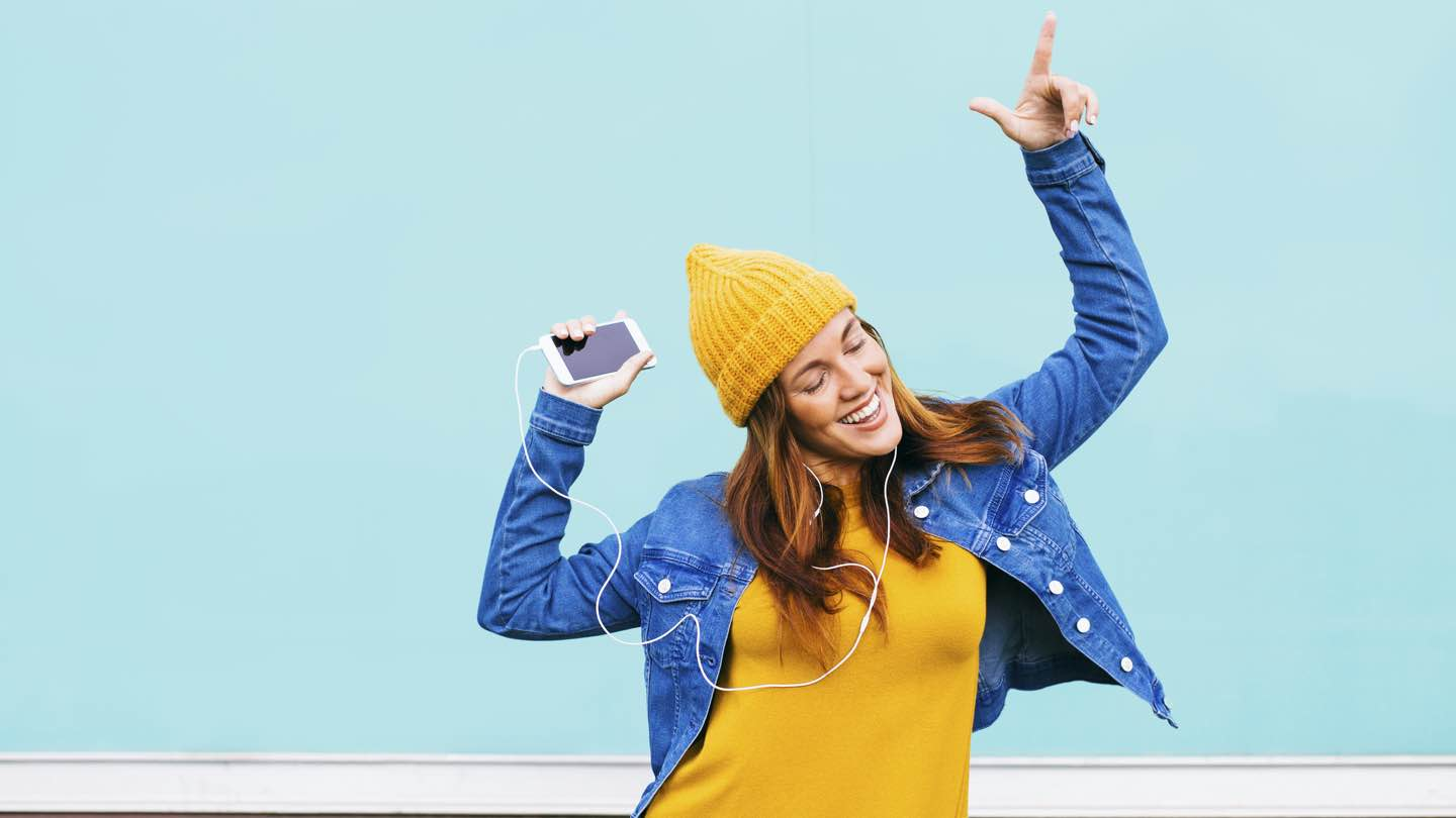 A woman wearing a yellow beanie, denim jacket and yellow jumper listens to music and dances in front of a light blue background.