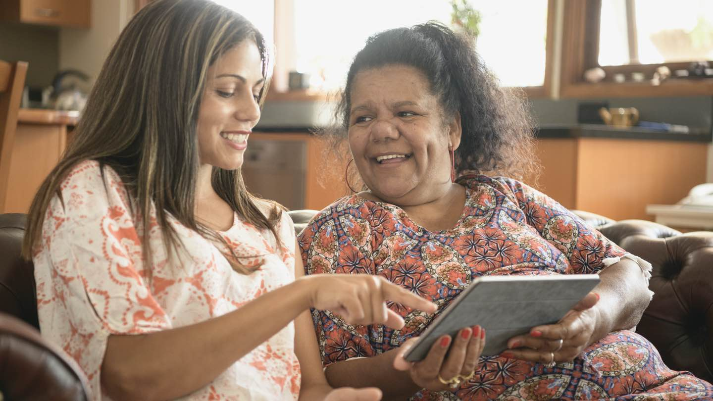 Two Indigenous Australian woman sit on sofa, looking at a tablet and reviewing finances.