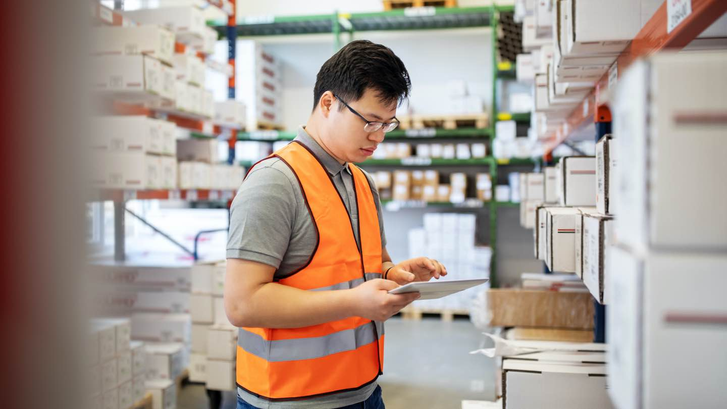 A man wearing an orange vest, working in a warehouse, reviews his finances on a tablet.