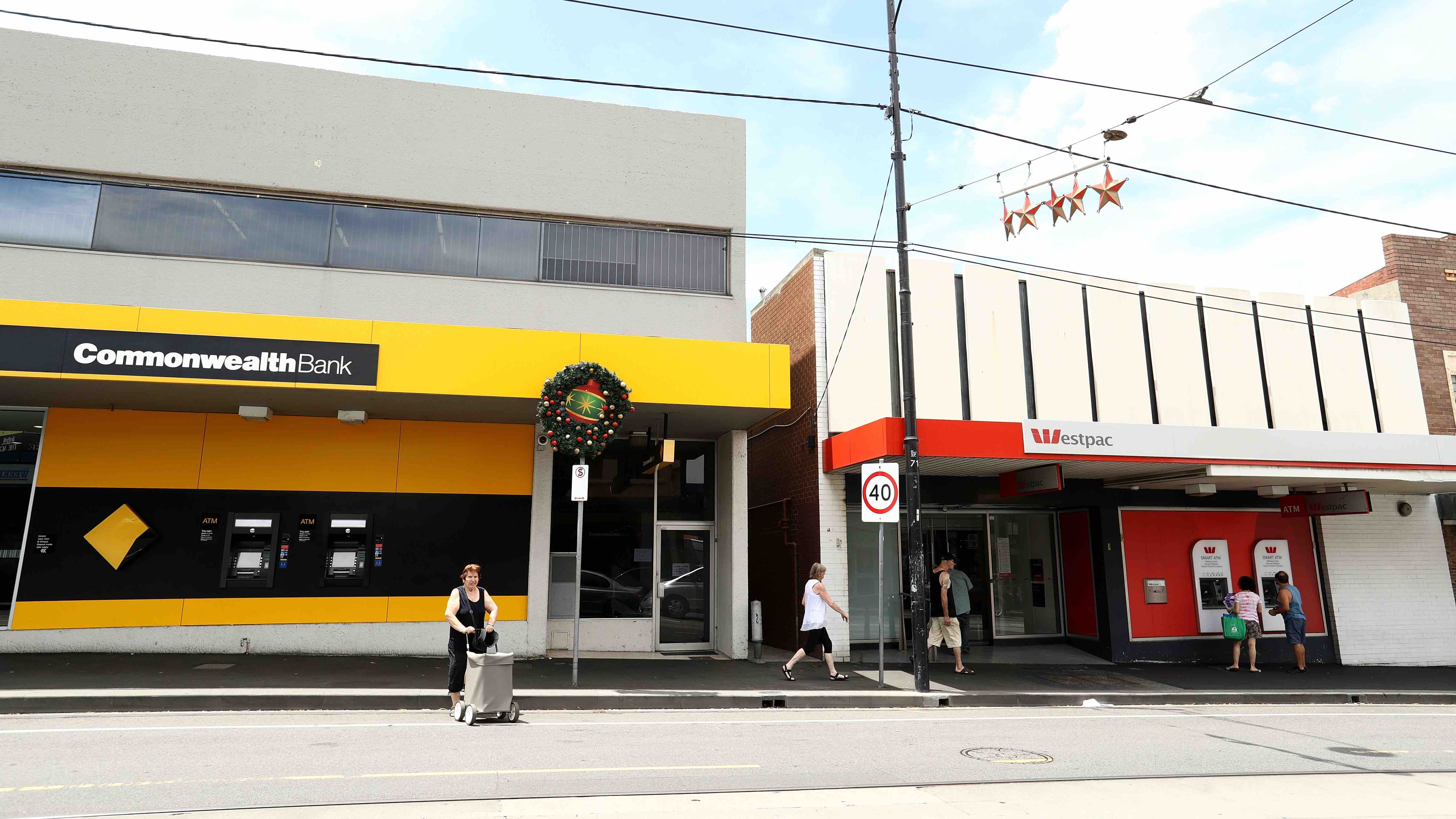 People walking past Commonwealth Bank and Westpac branches on anniversary of the banking royal commission.