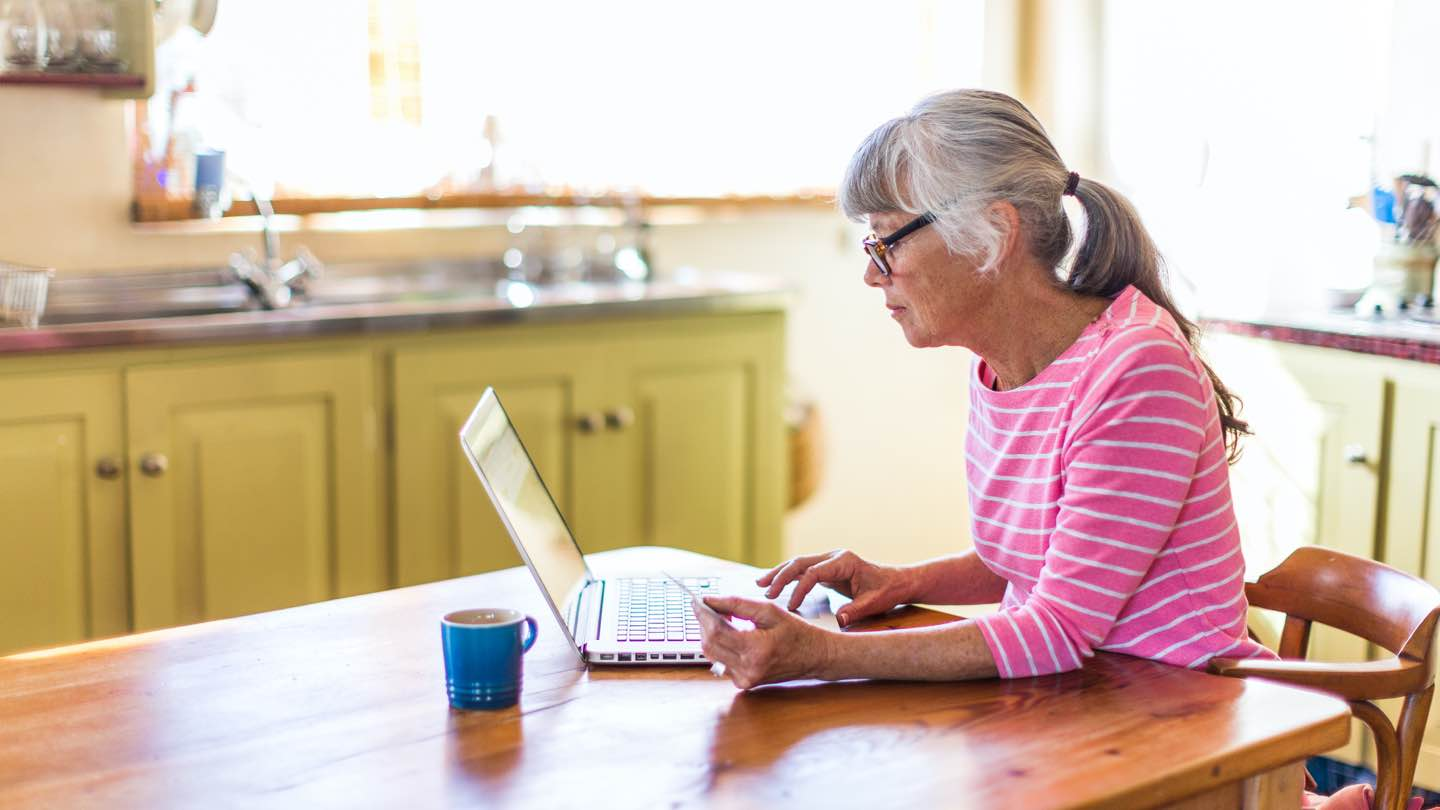 Side view of a woman with a pink and white stripy top and glasses, sitting at a kitchen table looking at her laptop. There is a blue mug resting on the table next to her.
