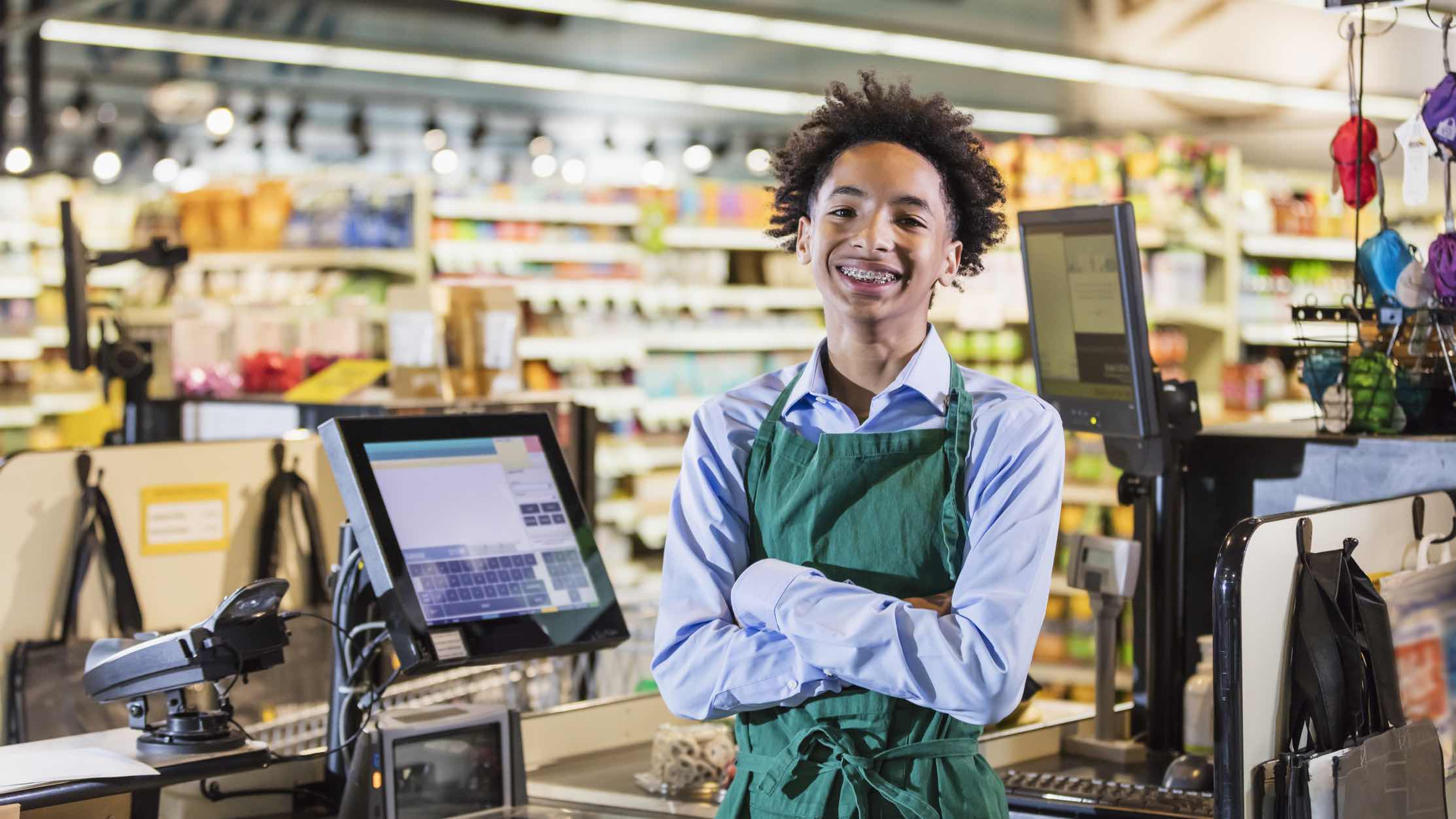 Teenager working behind the till in a supermarket at their first job.