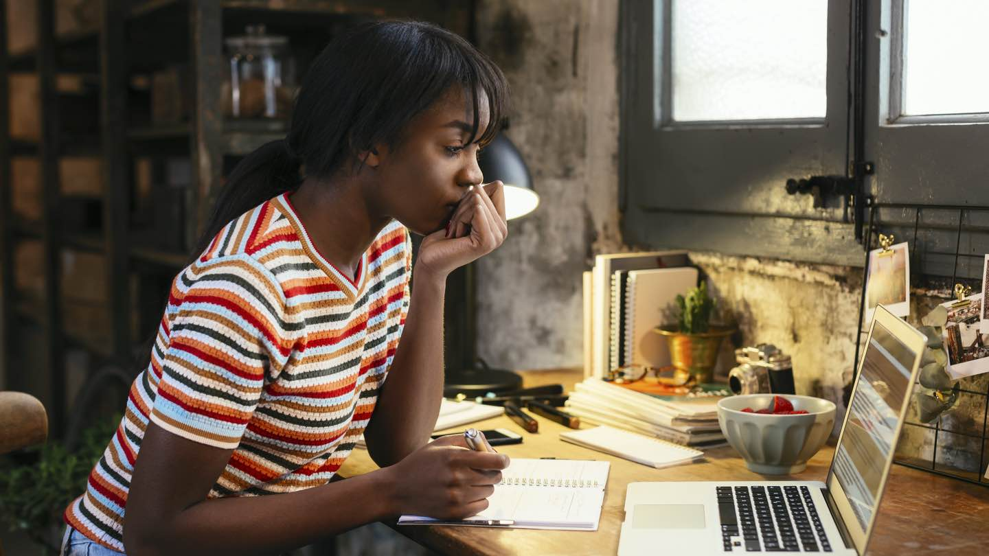 A woman wearing a stripy T-shirt sits at a desk, looking at a laptop.