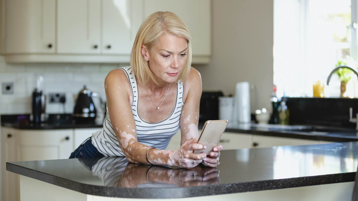 A woman leans against a kitchen counter, looking at news about credit reporting on her phone.