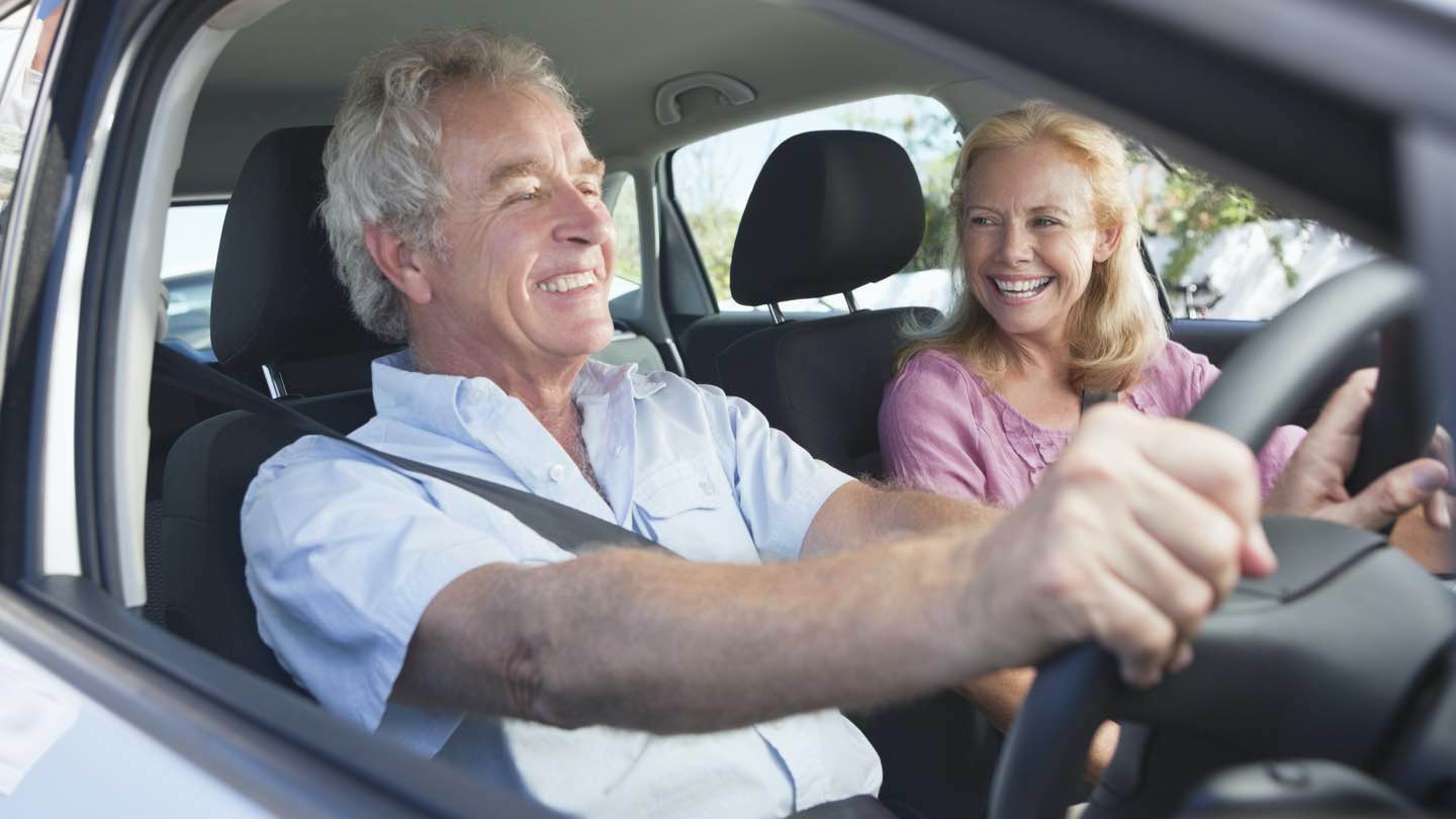 Older man and woman driving car.