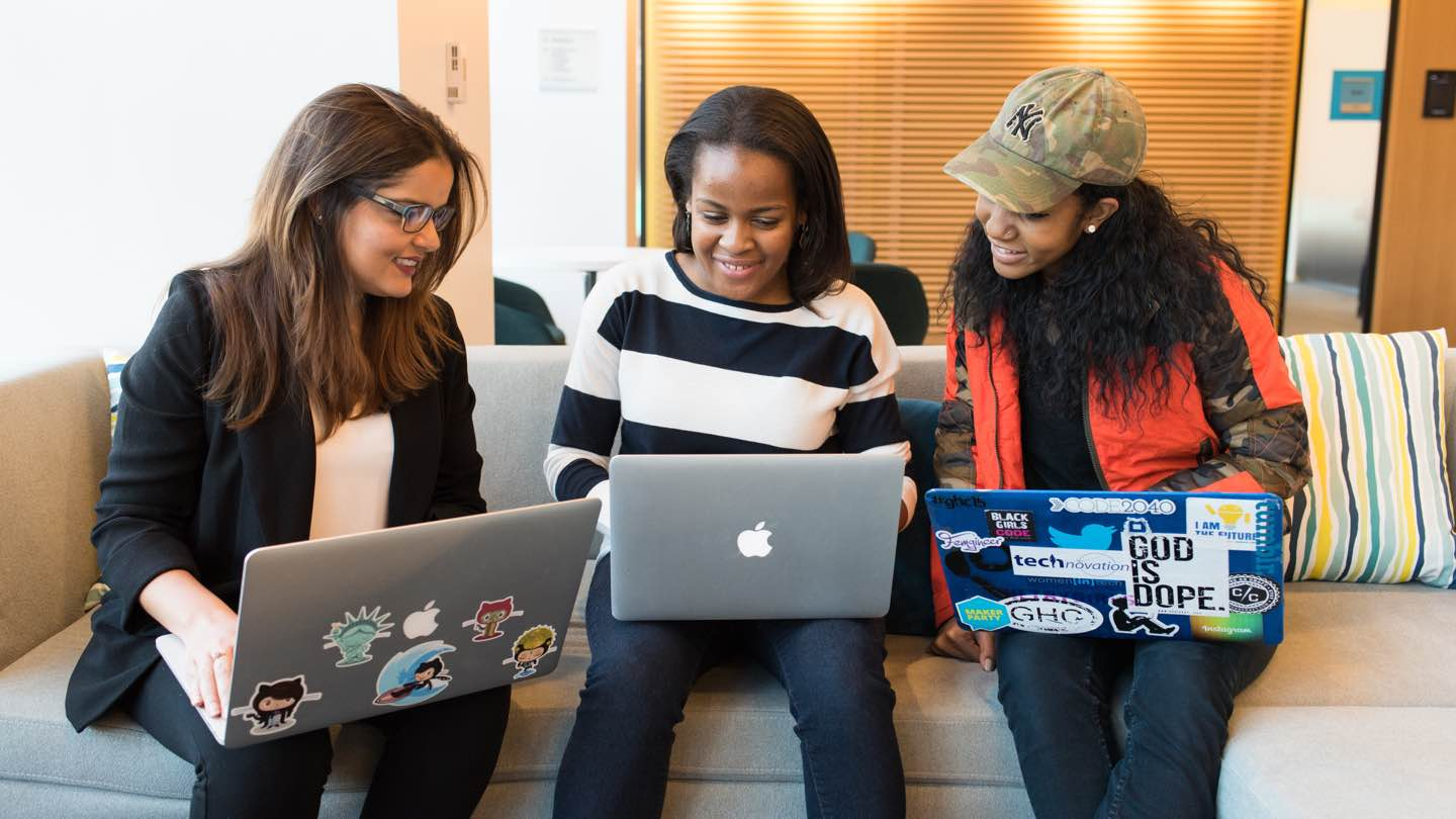 Three women sit on sofa smiling and looking at laptops.