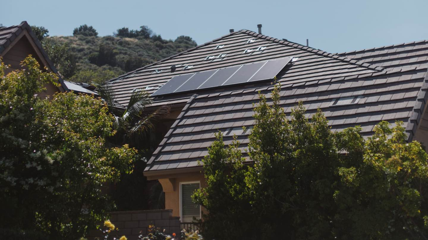 Home next to bushland with solar panels on the roof.