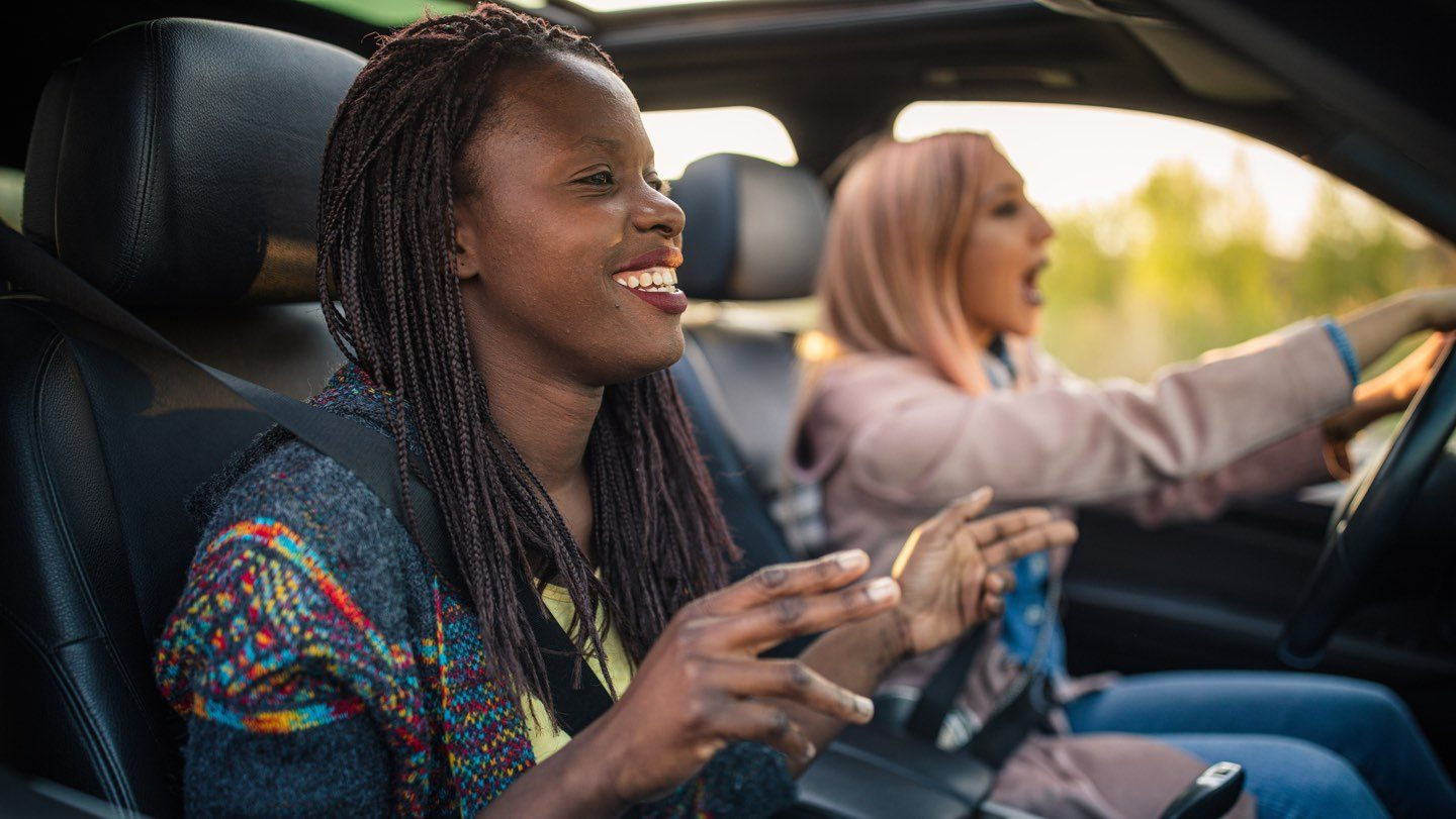 People driving, laughing and smiling after buying a new car interstate.