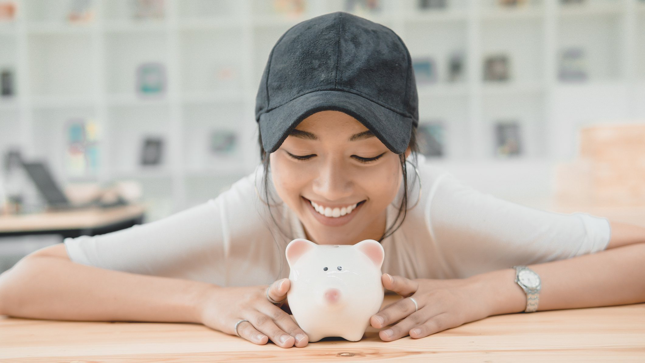 Person smiling at piggy bank, thinking about Teachers Mutual Bank award win.