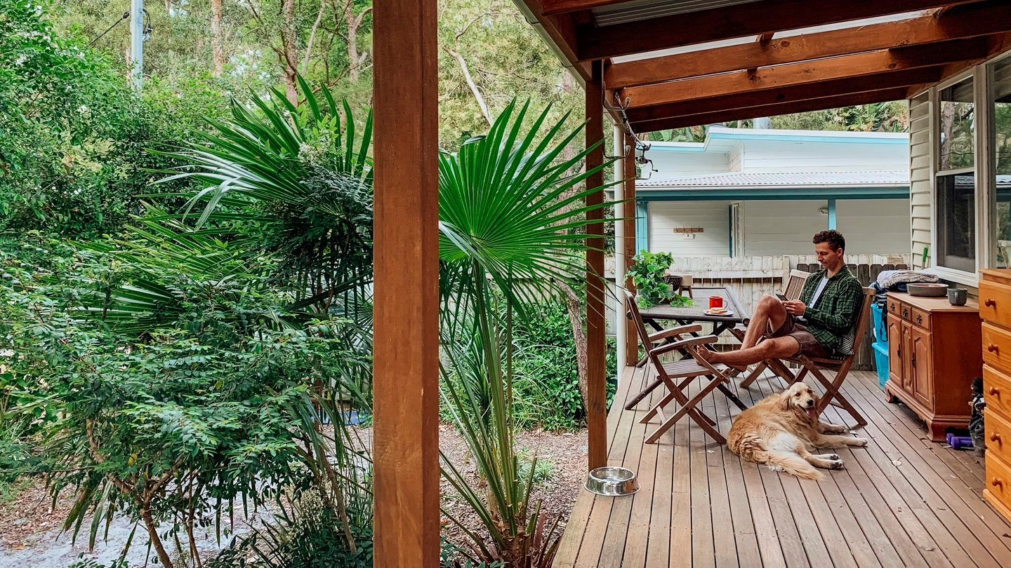 man-sitting-on-deck-of-house-with-dog