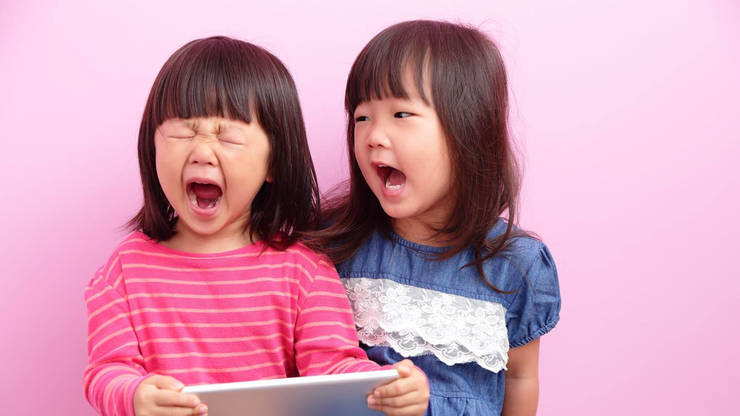 Two little girls scream while holding a tablet.