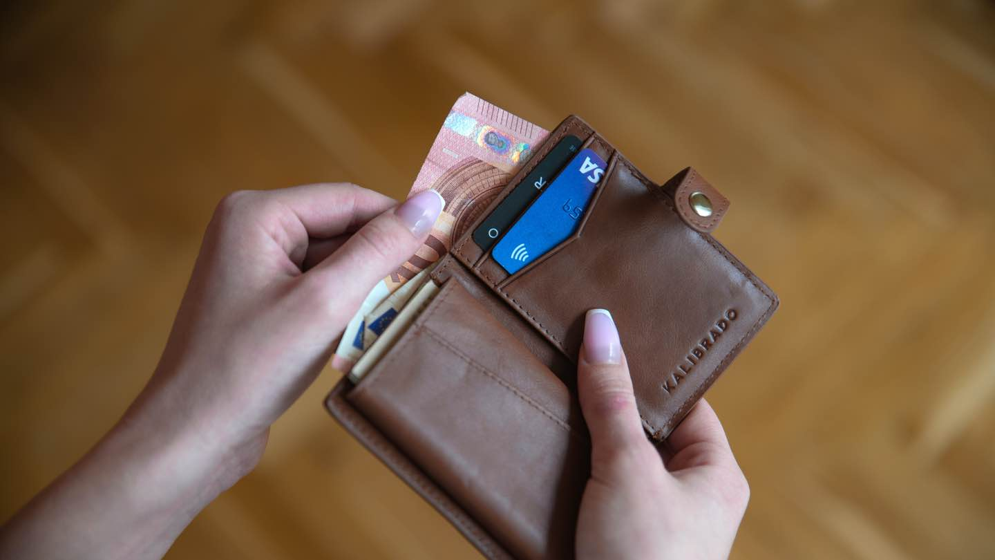 Hands holding an open wallet with bank cards and cash in it.