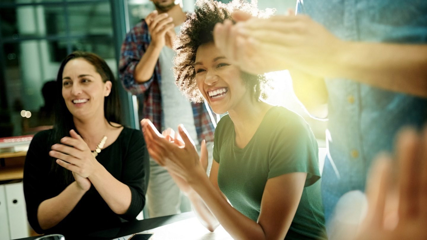 women in a company clapping