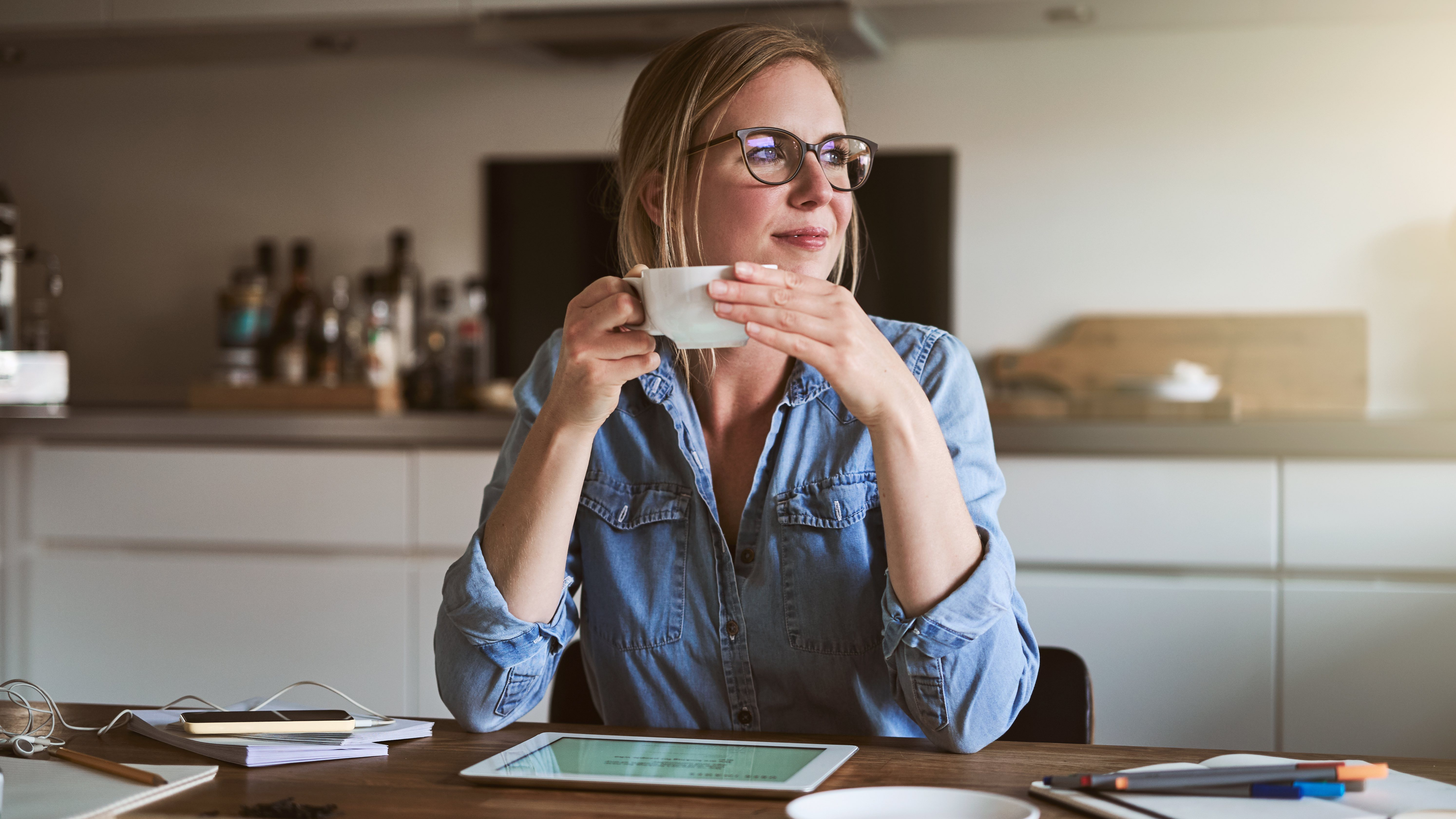 Woman sitting at home with documents and tablet, drinking a cup of tea and considering home ownership.