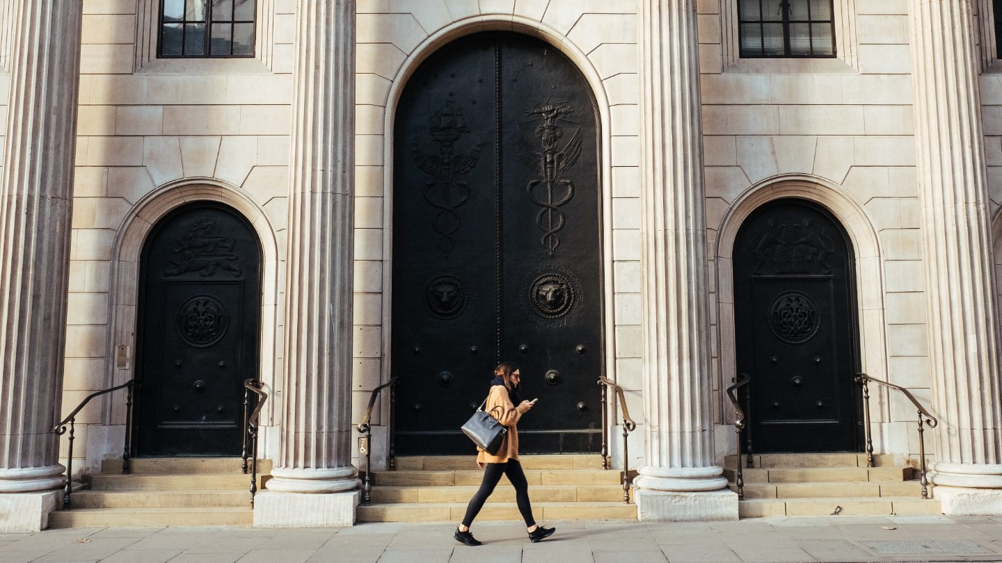 Woman walking past the Bank of England.