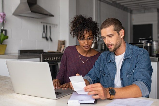 Couple sitting at a computer looking at bills and their finances as responsible lending laws axed.