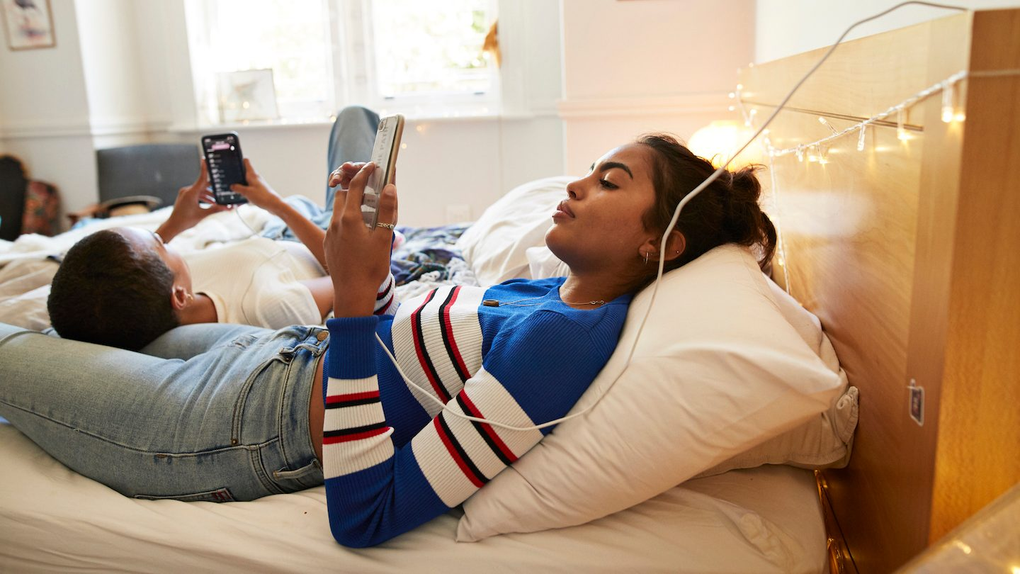 girls using phones in bed plugged in charging