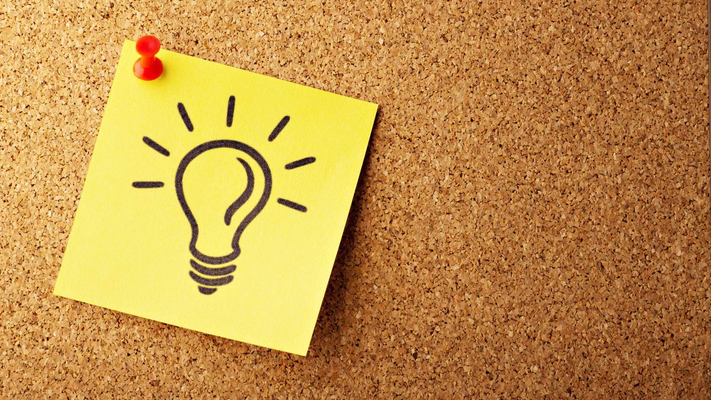 Post it note with light bulb, pinned to notice board.
