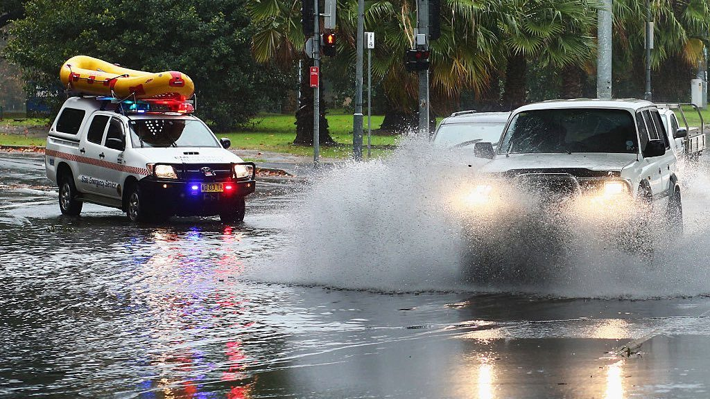 Cars driving near flood waters in historic NSW weather.