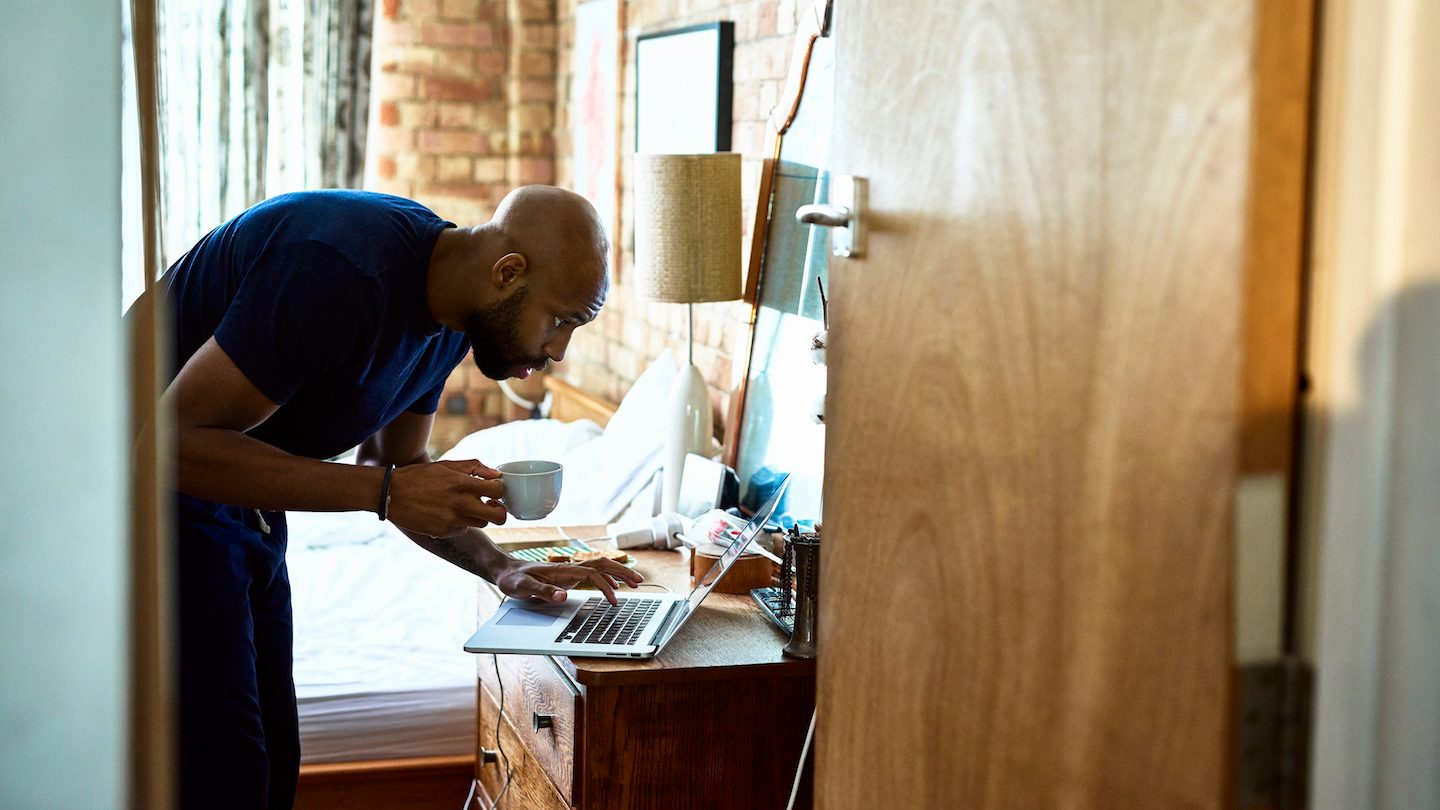 man in bedroom looking up debt consolidation loan on his laptop