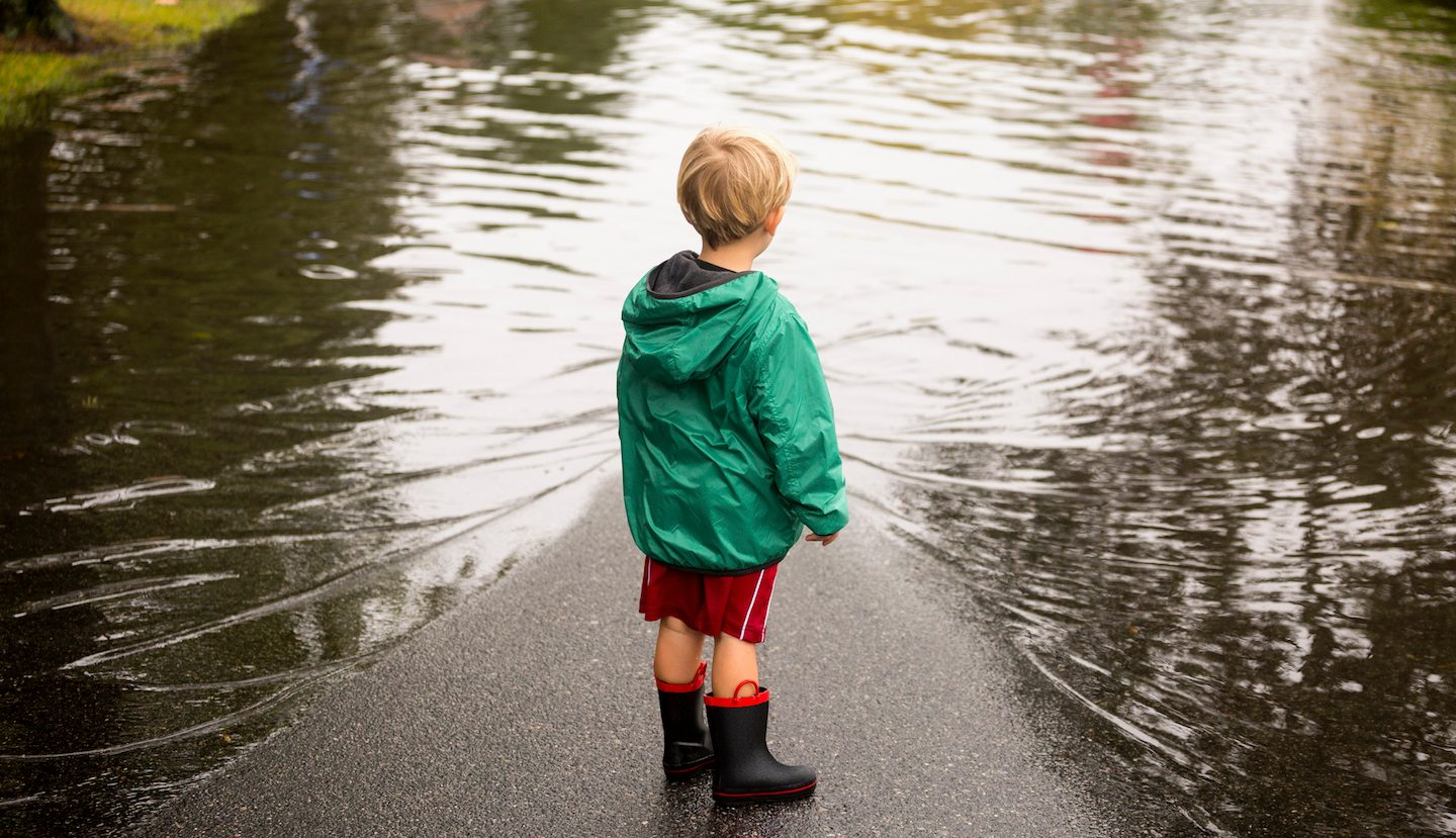 boy in gumboots looking at flood water in NSW