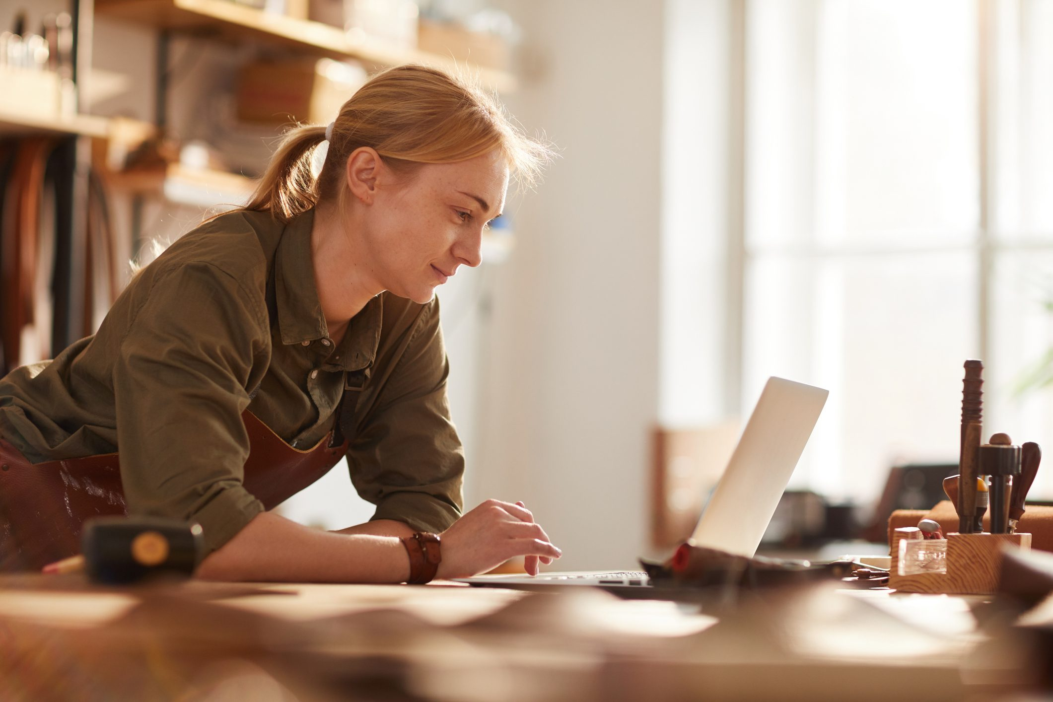 Woman business owner looking at laptop
