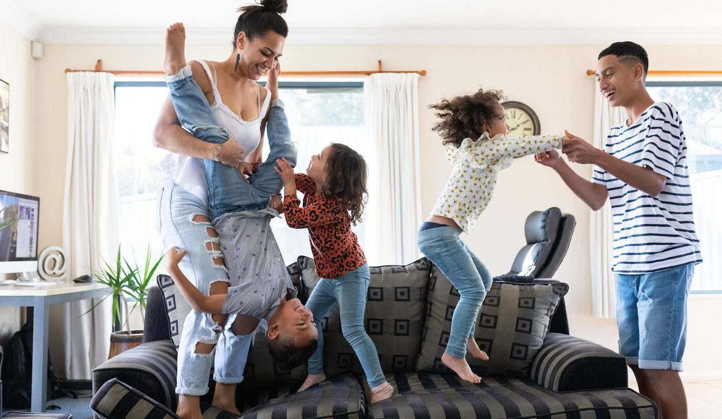family playing on sofa in new home bought with loan