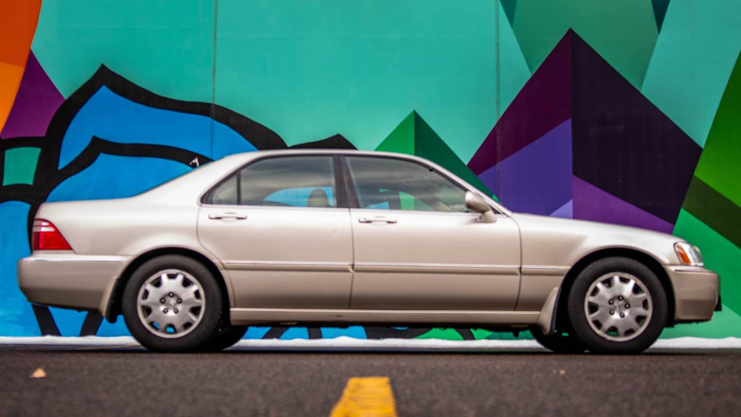 A silver car is parked in front of a brightly painted wall.