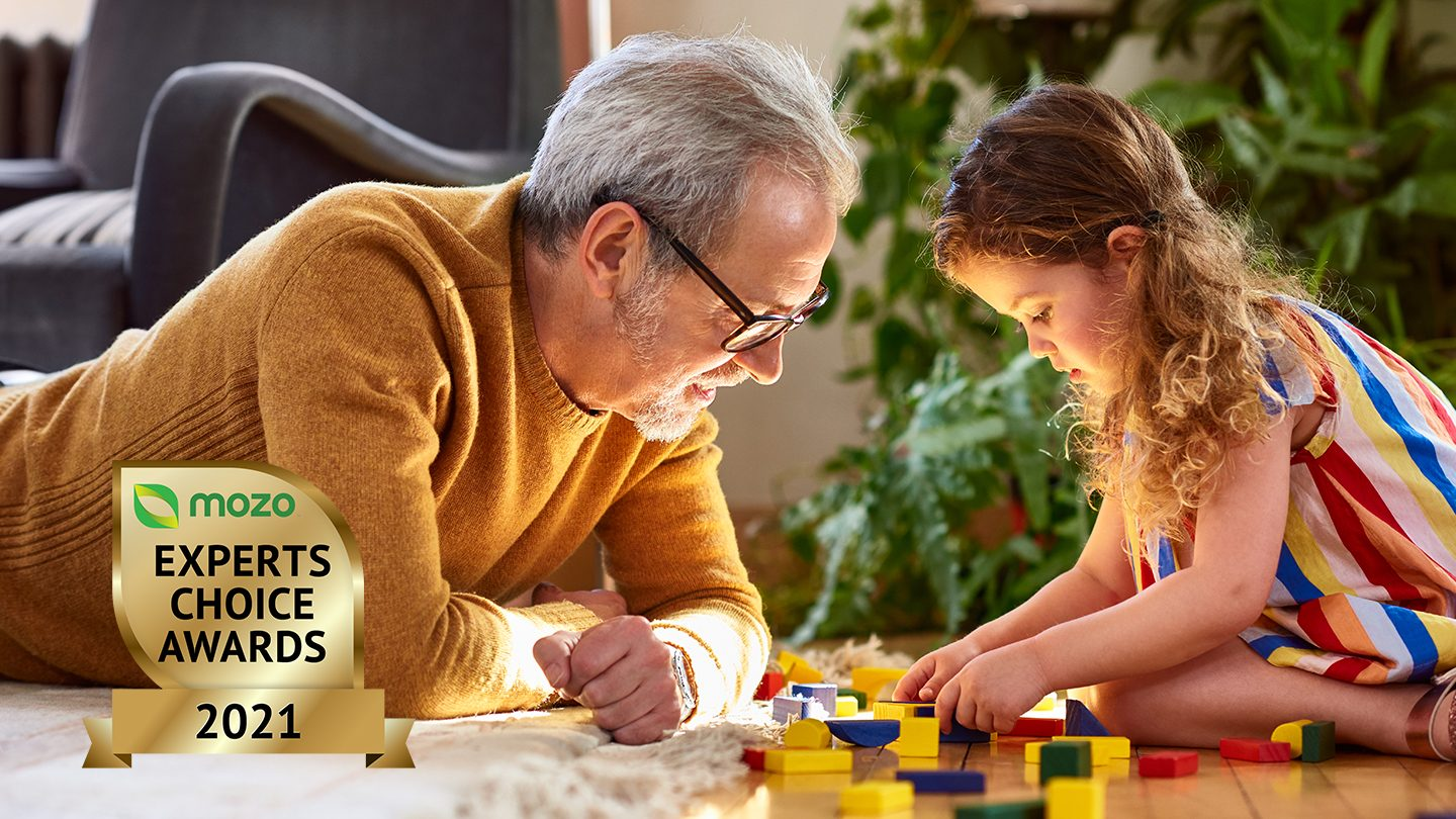A father and daughter sitting playing with lego bricks.