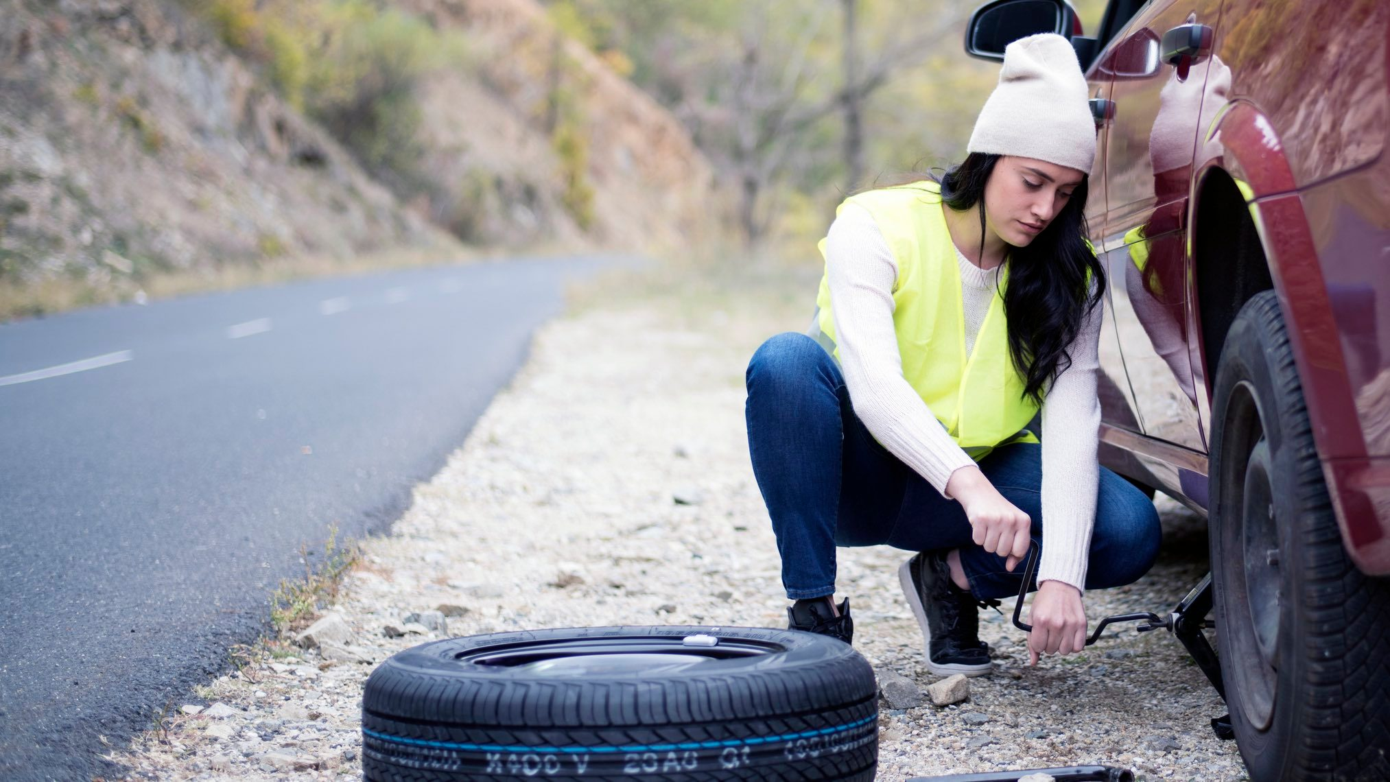 Woman with tyre insurance on the roadside changing a car tyre.