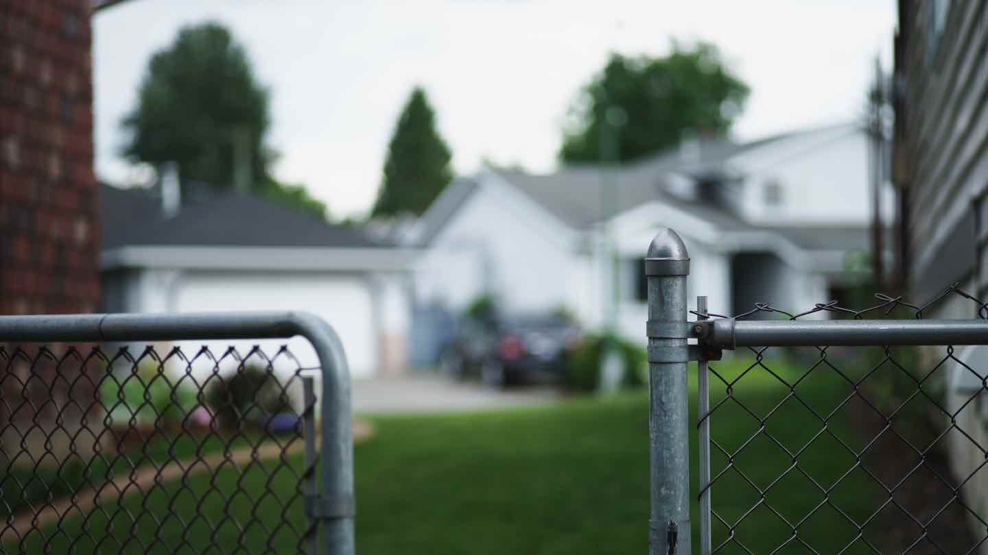 Picture of a home with security gates open in the foreground.