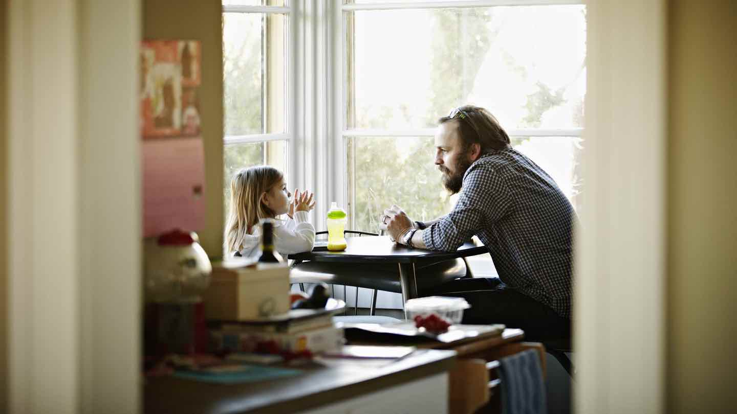 father and daughter sit at kitchen table