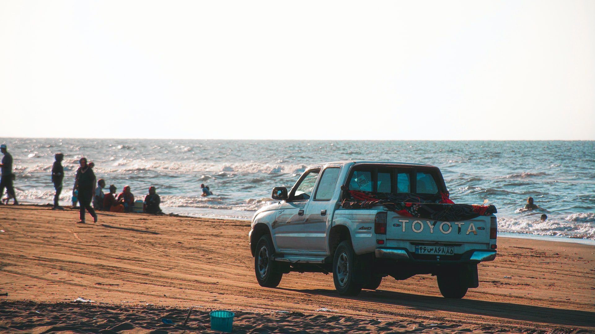 Toyota Hilux on a beach, driving with Toyota car insurance.