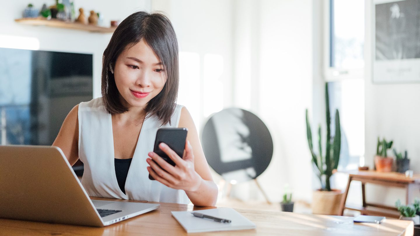 woman testing NBN speed on laptop and phone at home