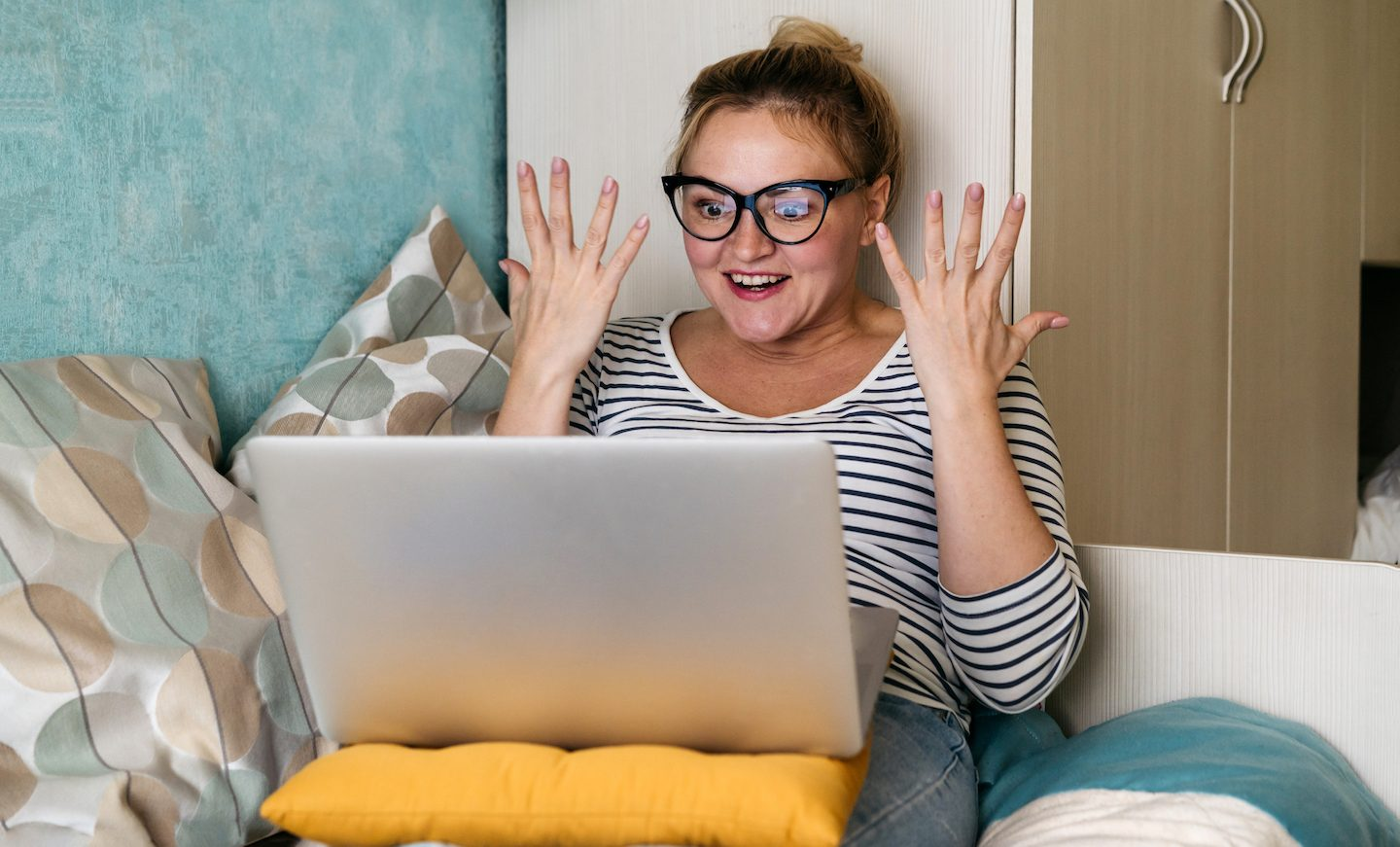 Excited woman on her laptop at home reading about the NBN.