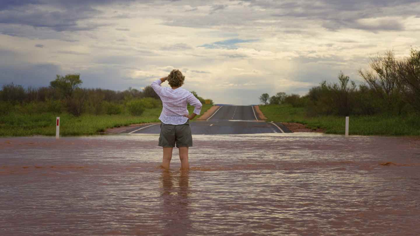 Woman stands on flooded road in Australia.