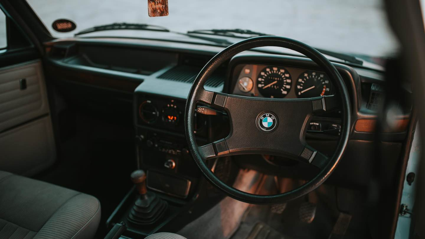 Inside of a BMW, shows steering wheel.