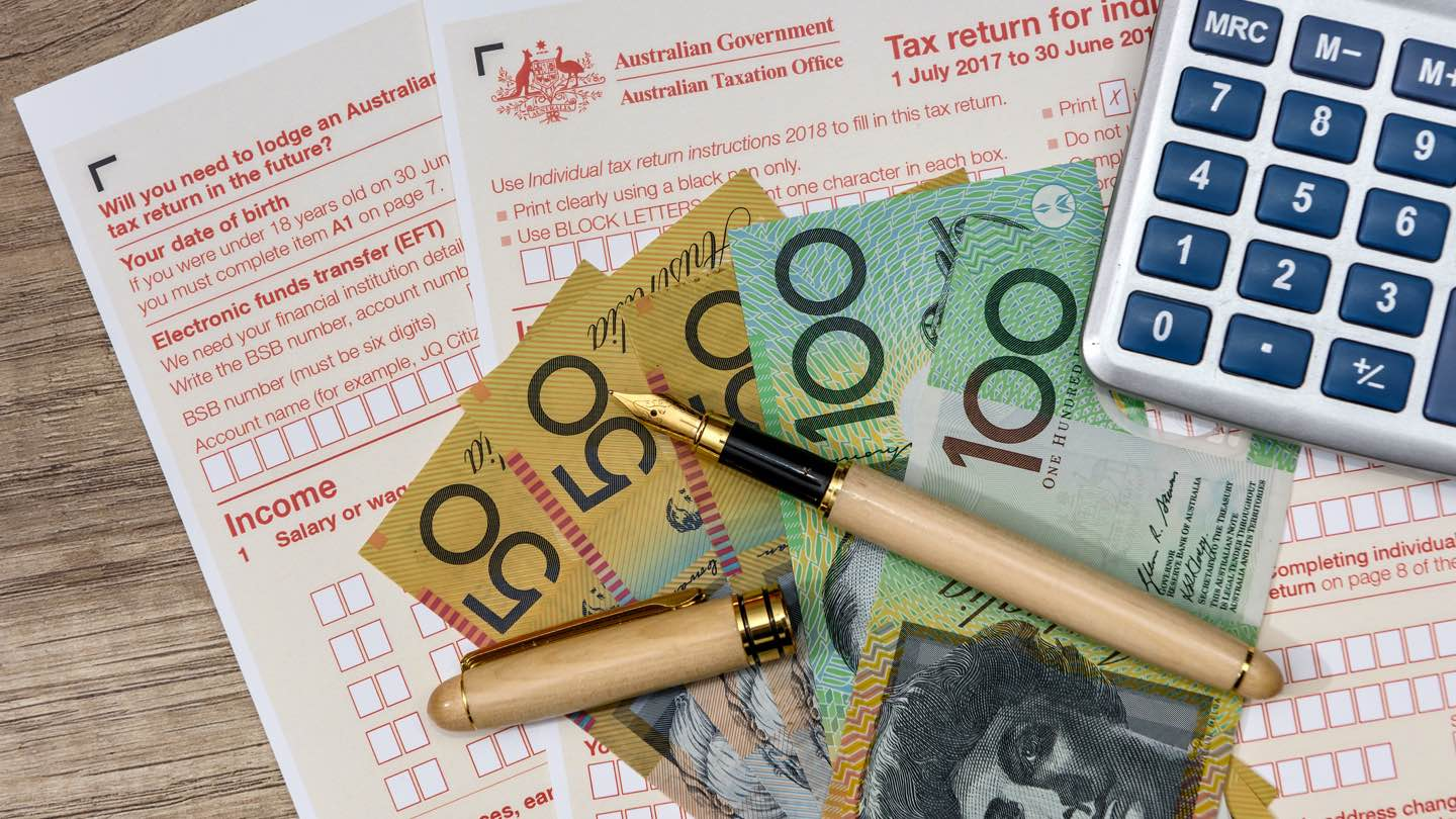 Australian tax documents with three $50 notes and two $100 notes on top and a fountain pen and calculator.