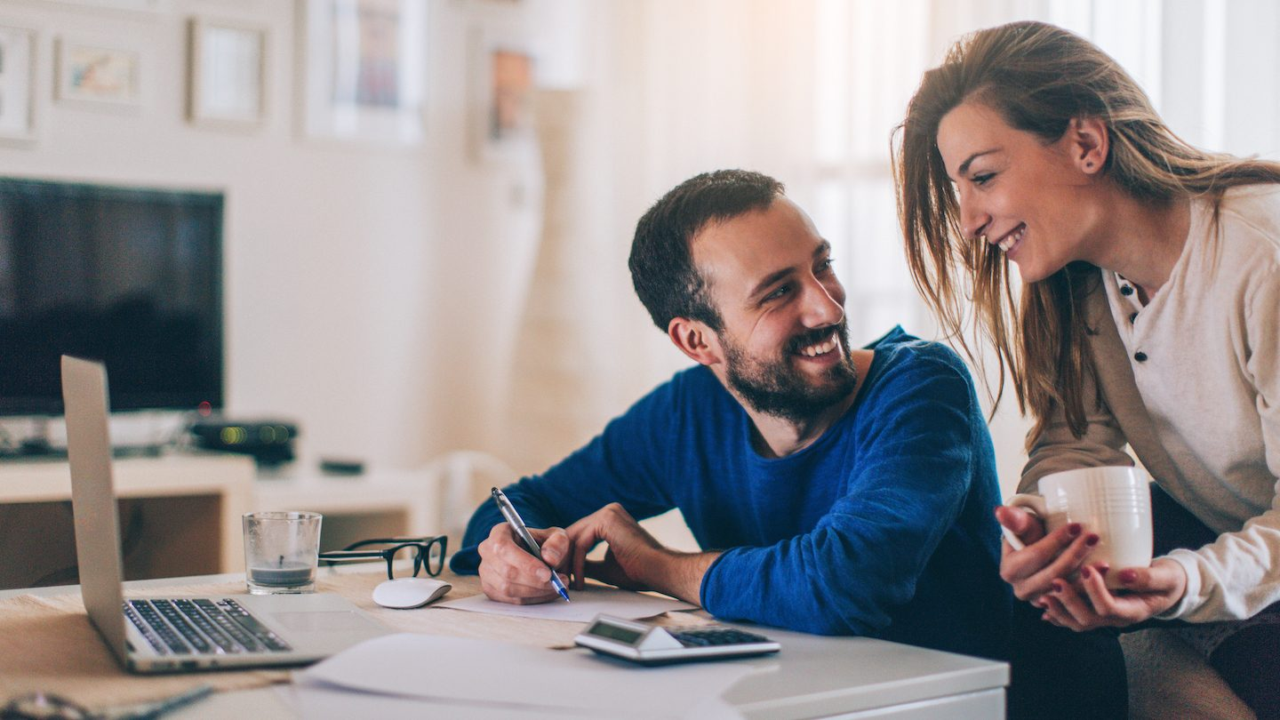 young couple at home consolidating their debt