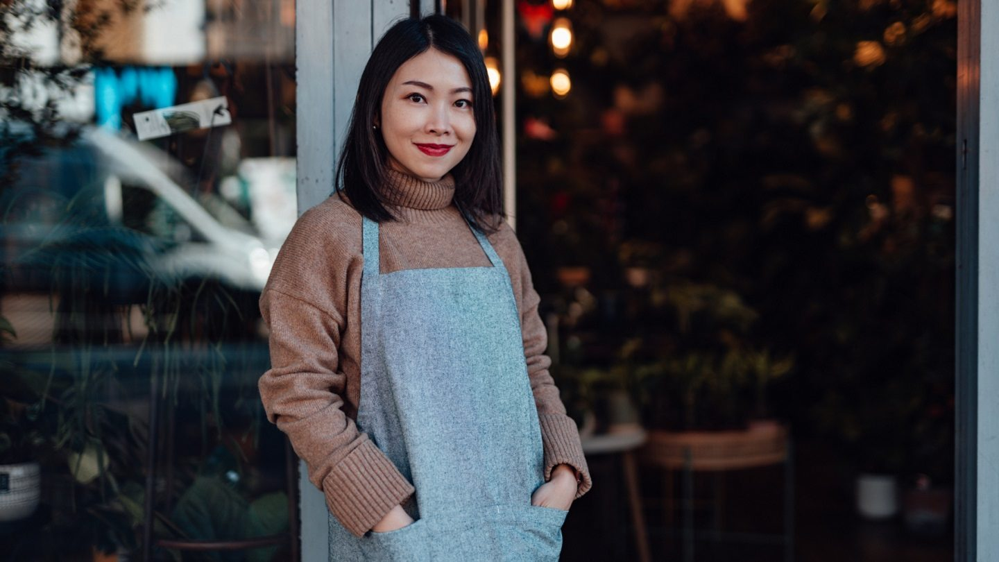 Female business owner standing in front of cafe
