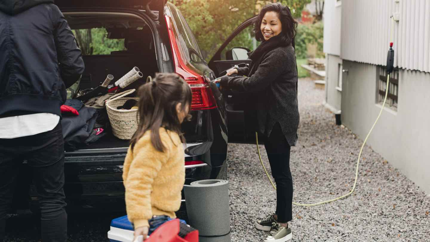 Mother stands charging electric vehicle with child and father emptying car boot in foreground.