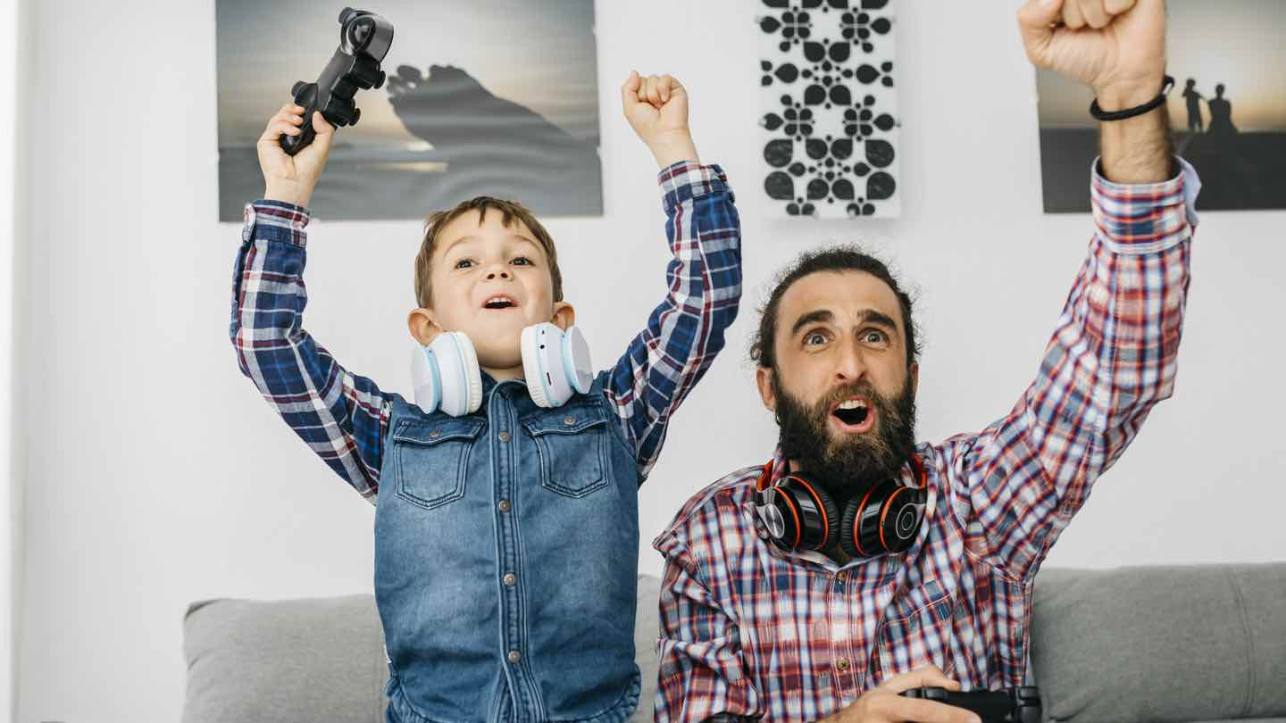 A father and son play Xbox together.