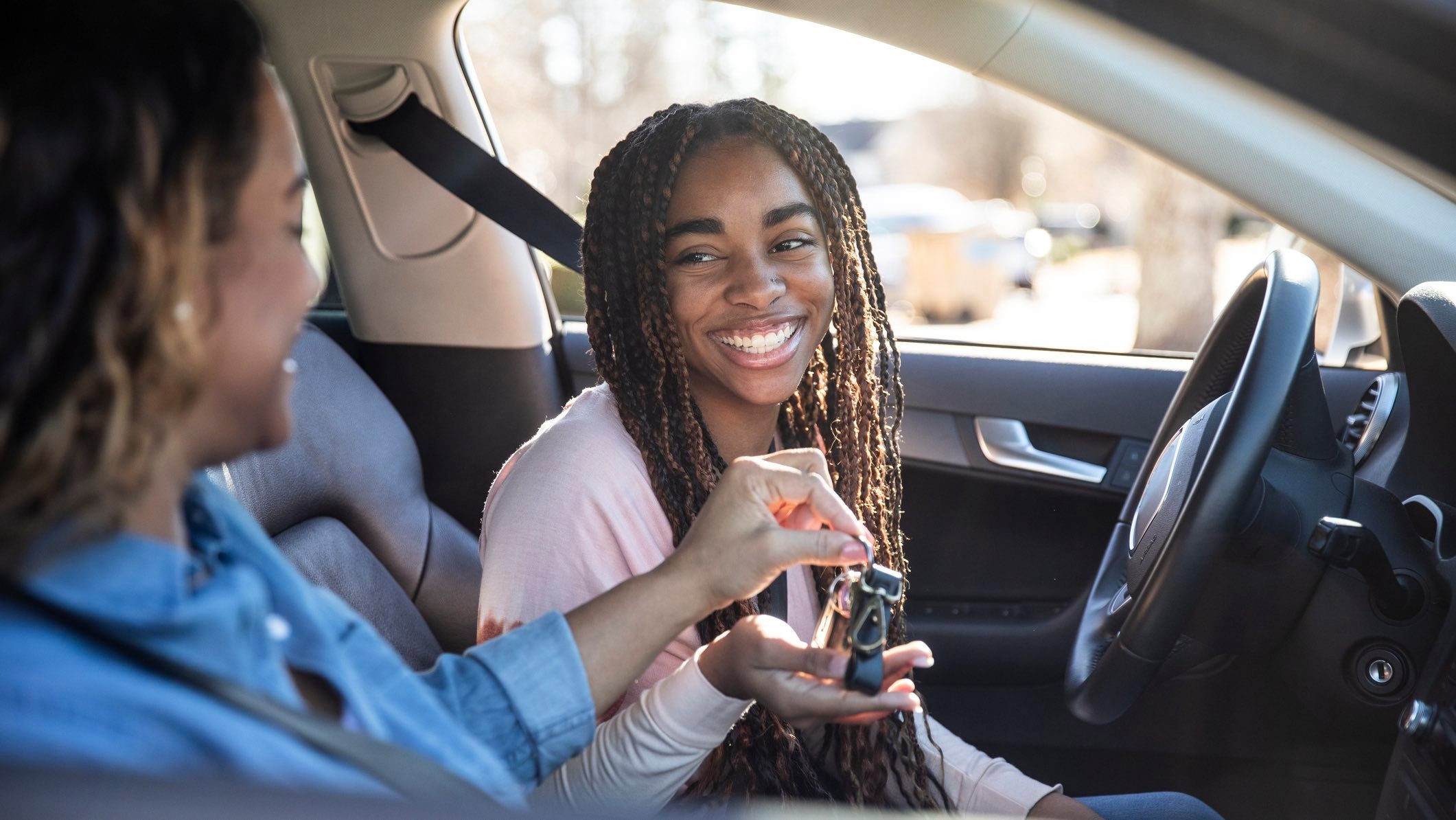 Person handing keys to a smiling young woman sitting in the drivers seat of a secondhand car.