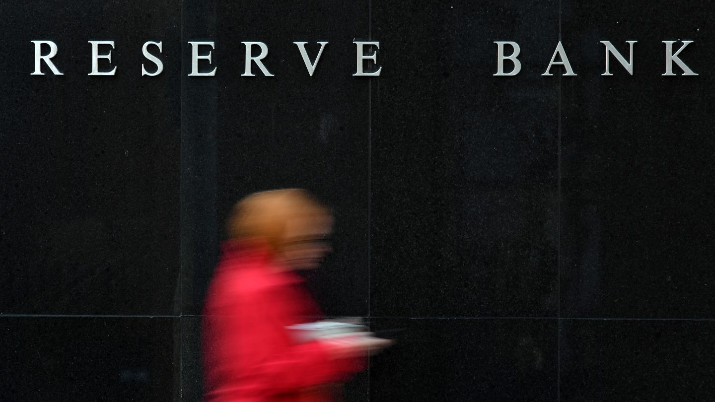 Person walking in front of the Reserve Bank of Australia.